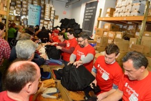 Volunteers stuff gloves, scarves, toques, toiletries and more into dufflebags during The Bargains Group's Project Winter Survival event on Saturday. The volunteers helped load up 3,000 bags for distribution to the city's homeless.