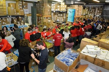 Volunteers form an assembly line stuffing cold weather and toiletry items into bags to be delivered to the homeless as part of the Bargain Group's annual Project Winter Survival event on Saturday.