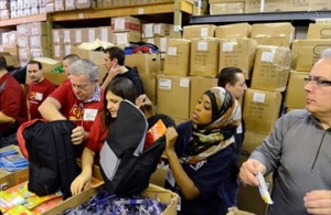Volunteers Samira Mohamed, right, Vanessa Reda and Paul Carter join an assembly line during The Bargains Group's annual Project Winter Survival event on Caledonia Road last year. Thousands of backpacks were filled with winter gear and personal care products for distribution to the homeless throughout the city. The 2014 event is scheduled for Saturday, Jan. 18.