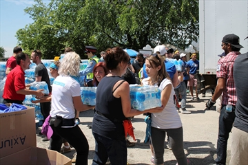 Volunteers help load bottles on to a truck during the 16th annual Project Water at The Bargains Group on Wednesday. Hundreds of participants were on hand to move water and survival kits onto vehicles to be distributed to the homeless and people in need.